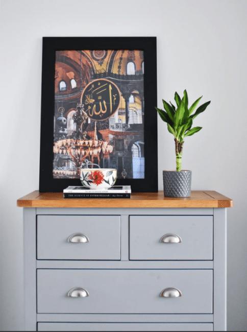 Šedá industriální komoda s dekoracemi v podobě květiny, dekorační misky, knih a obrazuu